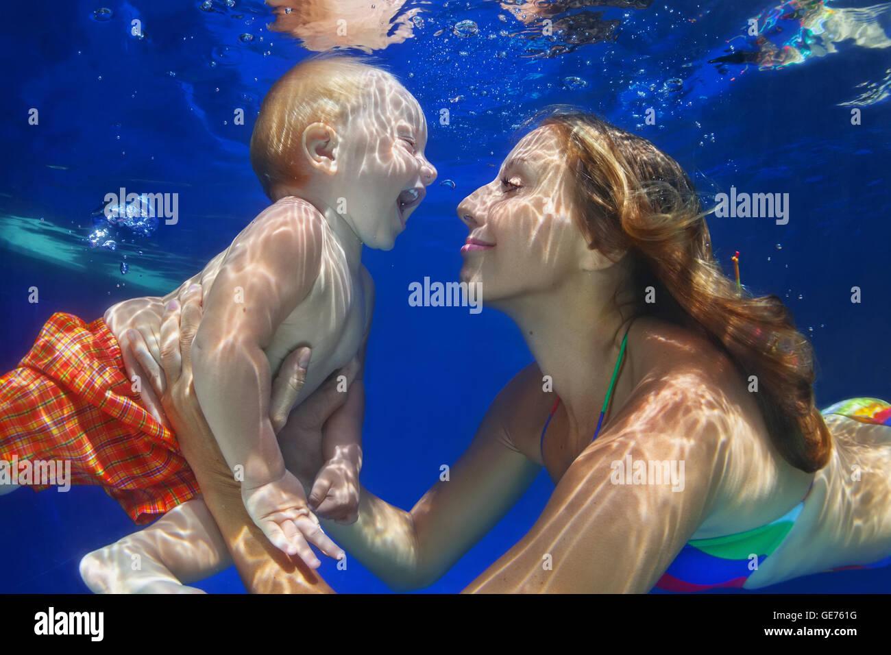 - Mère de famille heureuse, bébé apprend à nager et plonger sous l'eau avec in piscine. Photo Stock