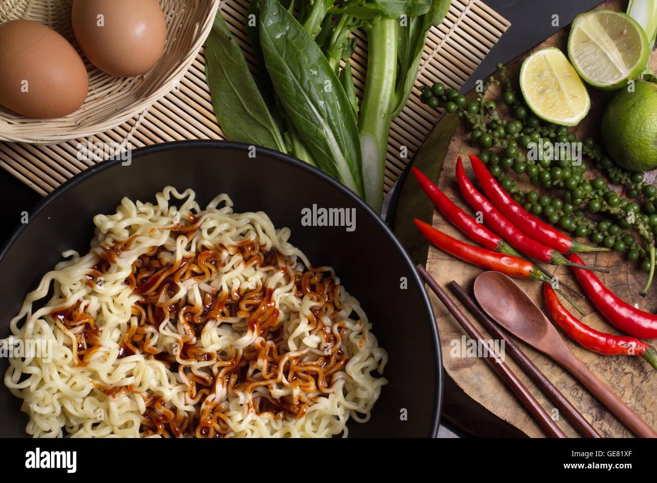 Les nouilles dans un bol noir garnie sur table de cuisine Photo Stock