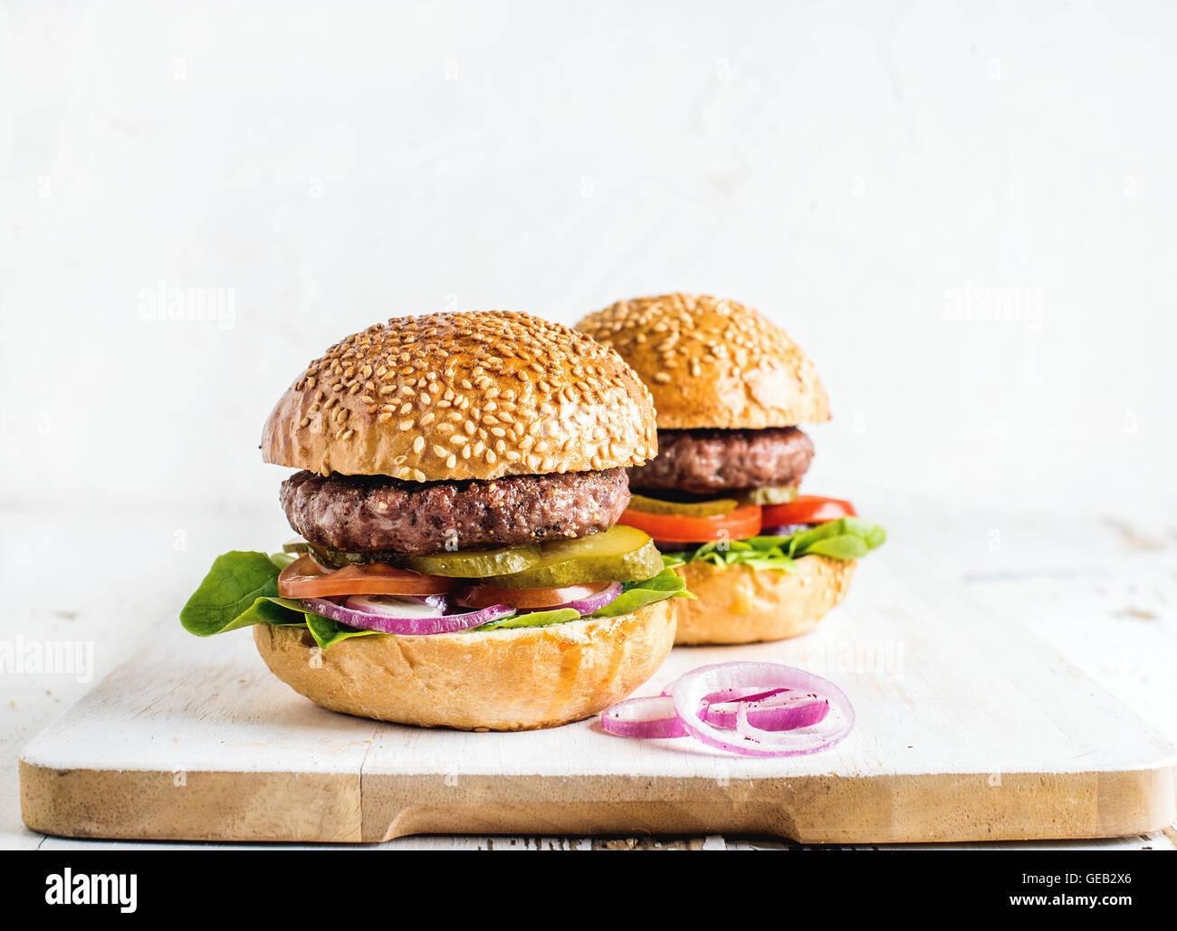 Des burgers sur sol en bois servant de sélection avec des oignons. Photo Stock