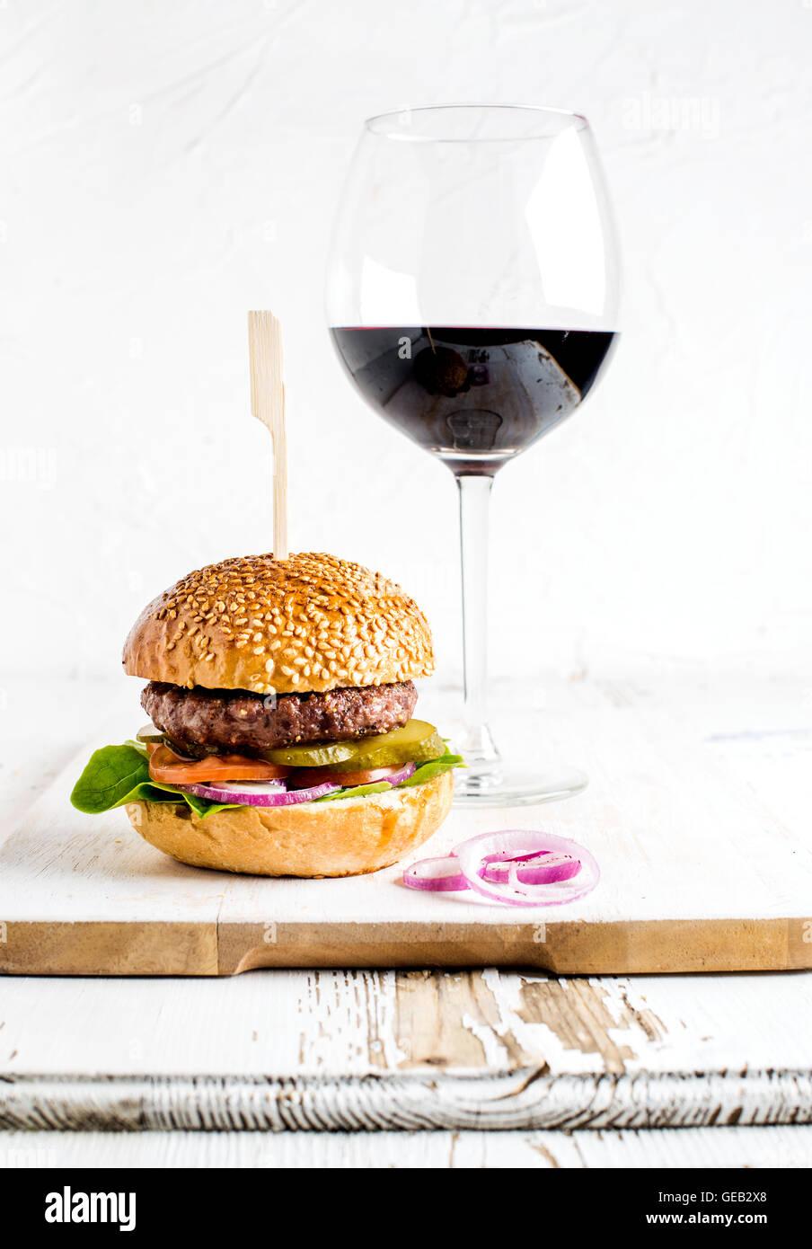 Burger maison en bois servant à bord avec des oignons et un verre de vin rouge Photo Stock