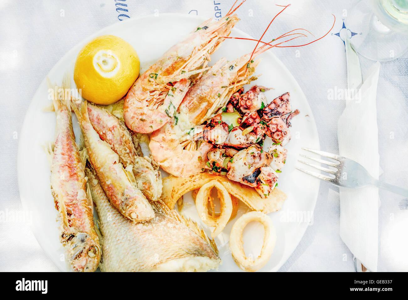 Les fruits de mer cuits sur la plaque avec le citron et le vin Photo Stock