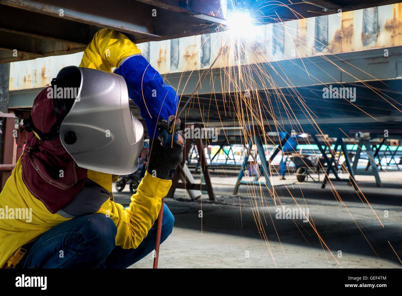 Travailleur de l'industrie de l'acier à souder pour réparer les structures de conteneurs dans Photo Stock