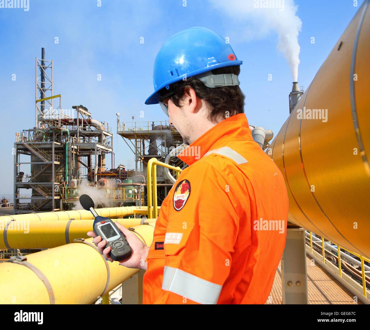 Un ingénieur de l'environnement surveille les niveaux de bruit à une usine de traitement chimique Photo Stock