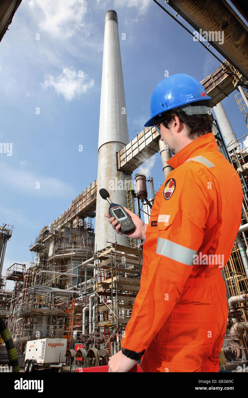 Un ingénieur de l'environnement surveille les niveaux de bruit à une raffinerie de pétrole au Photo Stock