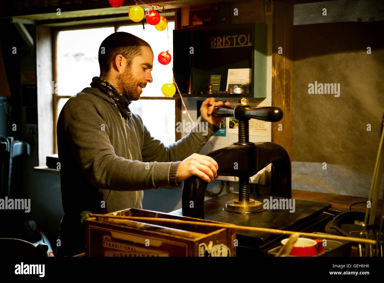 Un homme à l'aide d'une presse à imprimer pour créer des panneaux imprimés sur linoléum. Photo Stock