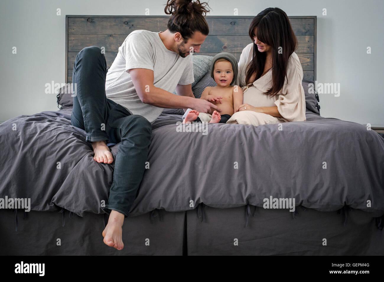 Un jeune couple et leur jeune fils, assis sur leur lit. Banque D'Images