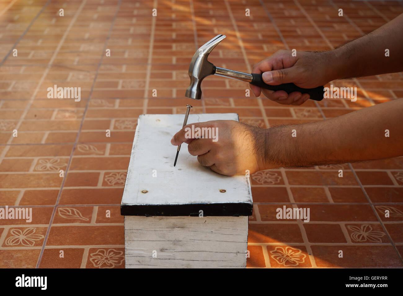 Carpenter supprimera l'ongle avec un marteau sur le bois blanc Banque D'Images