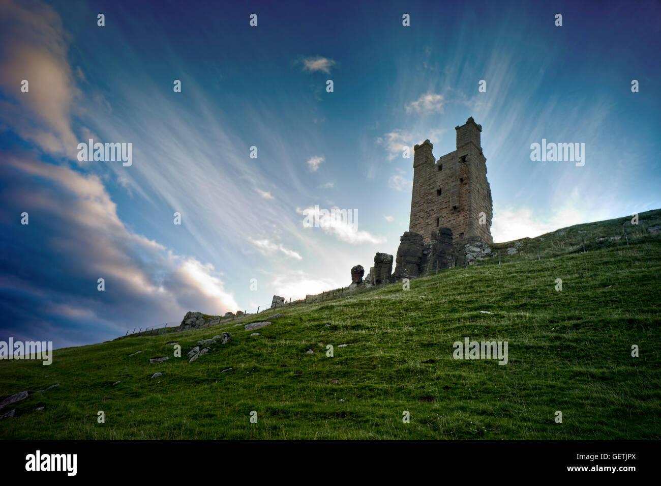 Château de Dunstanburgh perché sur la pointe. Photo Stock
