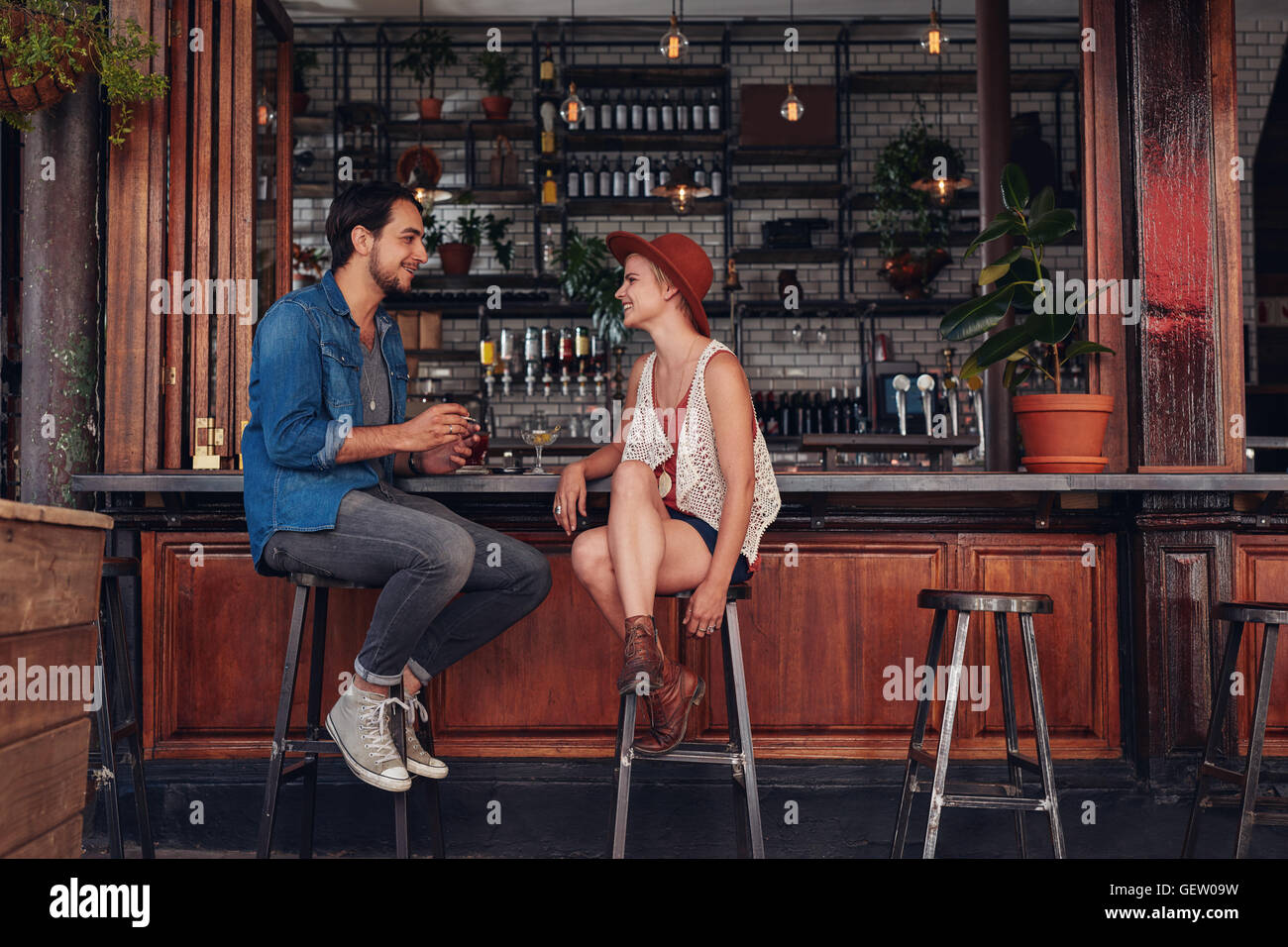 Shot of young couple sitting at cafe comptoir. Jeune homme et femme du coffee shop. Photo Stock