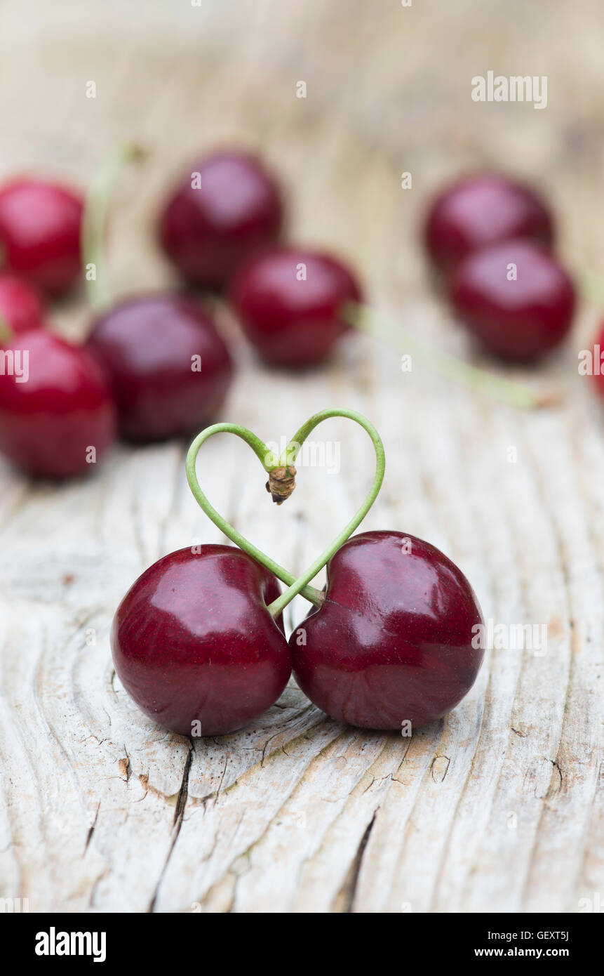 Cerises cueillies love heart sur bois Photo Stock