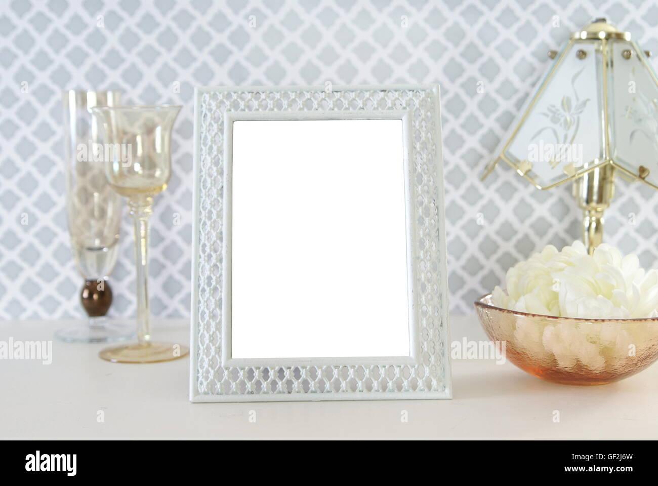 Cadre photo style vintage blanc avec des verres et de la décoration organisé près de lui. Banque D'Images