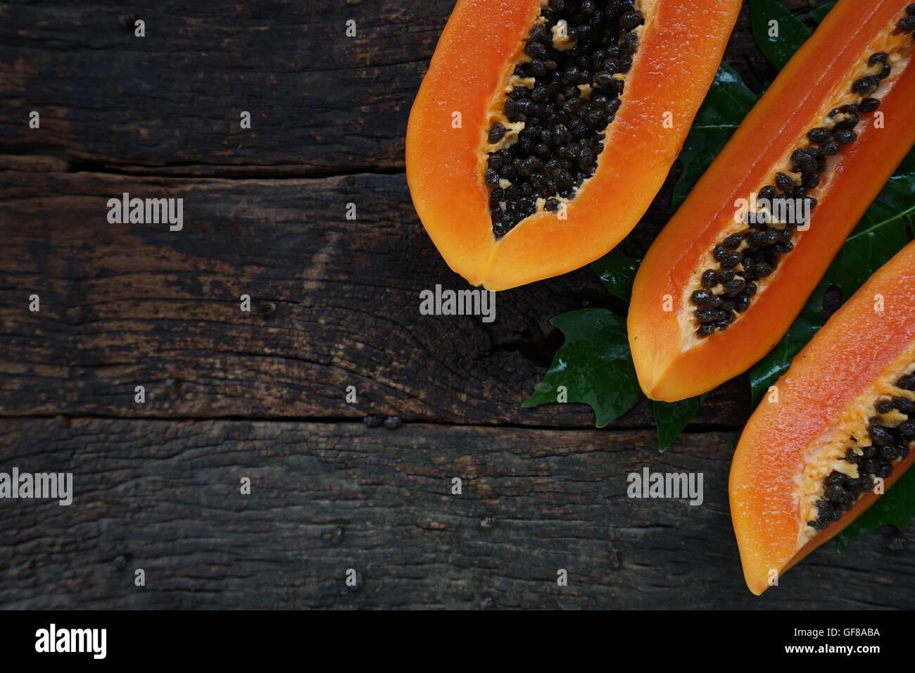 Vue de dessus de la papaye mûre avec feuille verte sur fond de bois ancien. Photo Stock