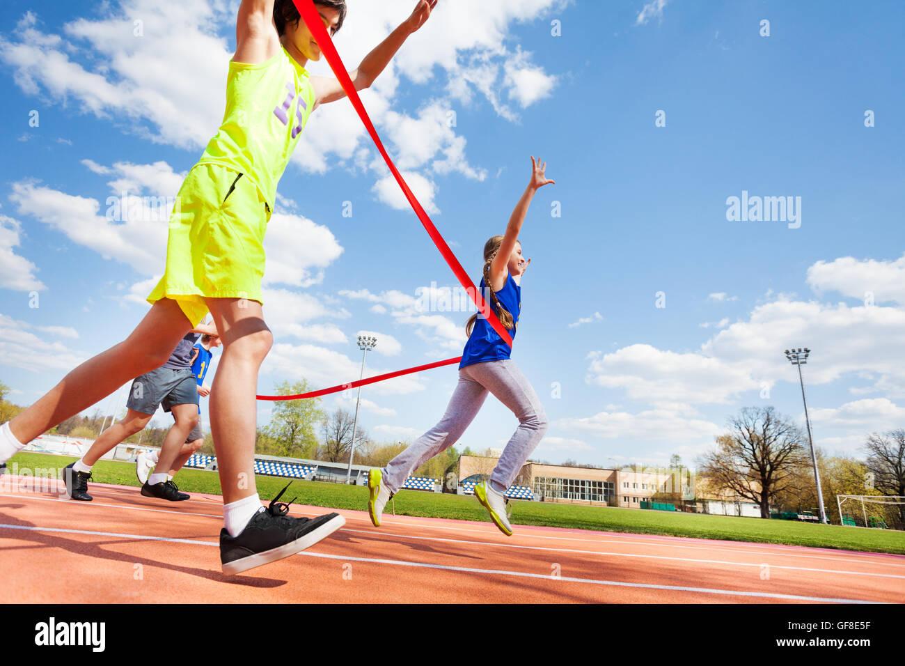 Happy girl crossing ligne d'arrivée sur le champ de courses Photo Stock