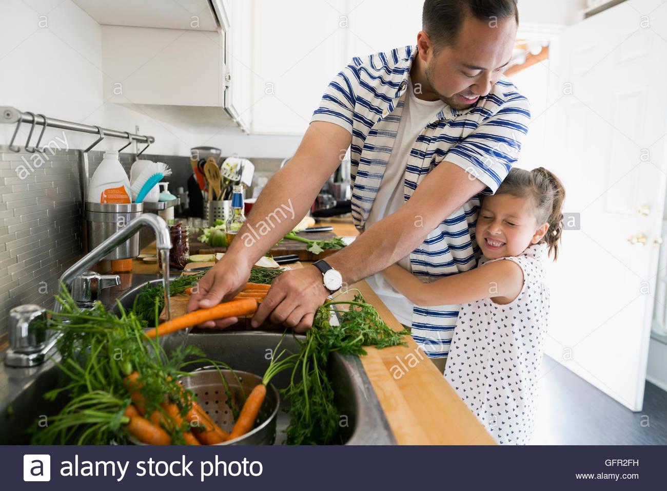 Daughter hugging père et la cuisson des carottes à laver évier de cuisine Photo Stock