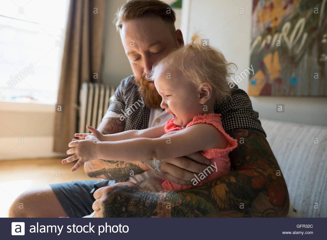 Père de tatouages holding fille pleurer Photo Stock