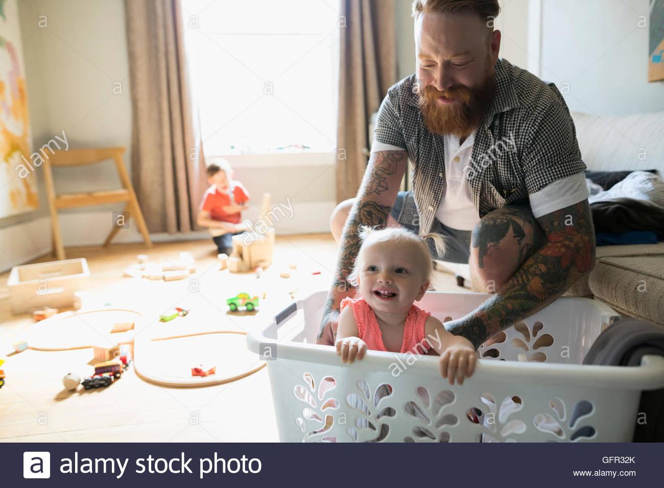 Père heureux avec sa fille à l'intérieur de panier de blanchisserie Photo Stock