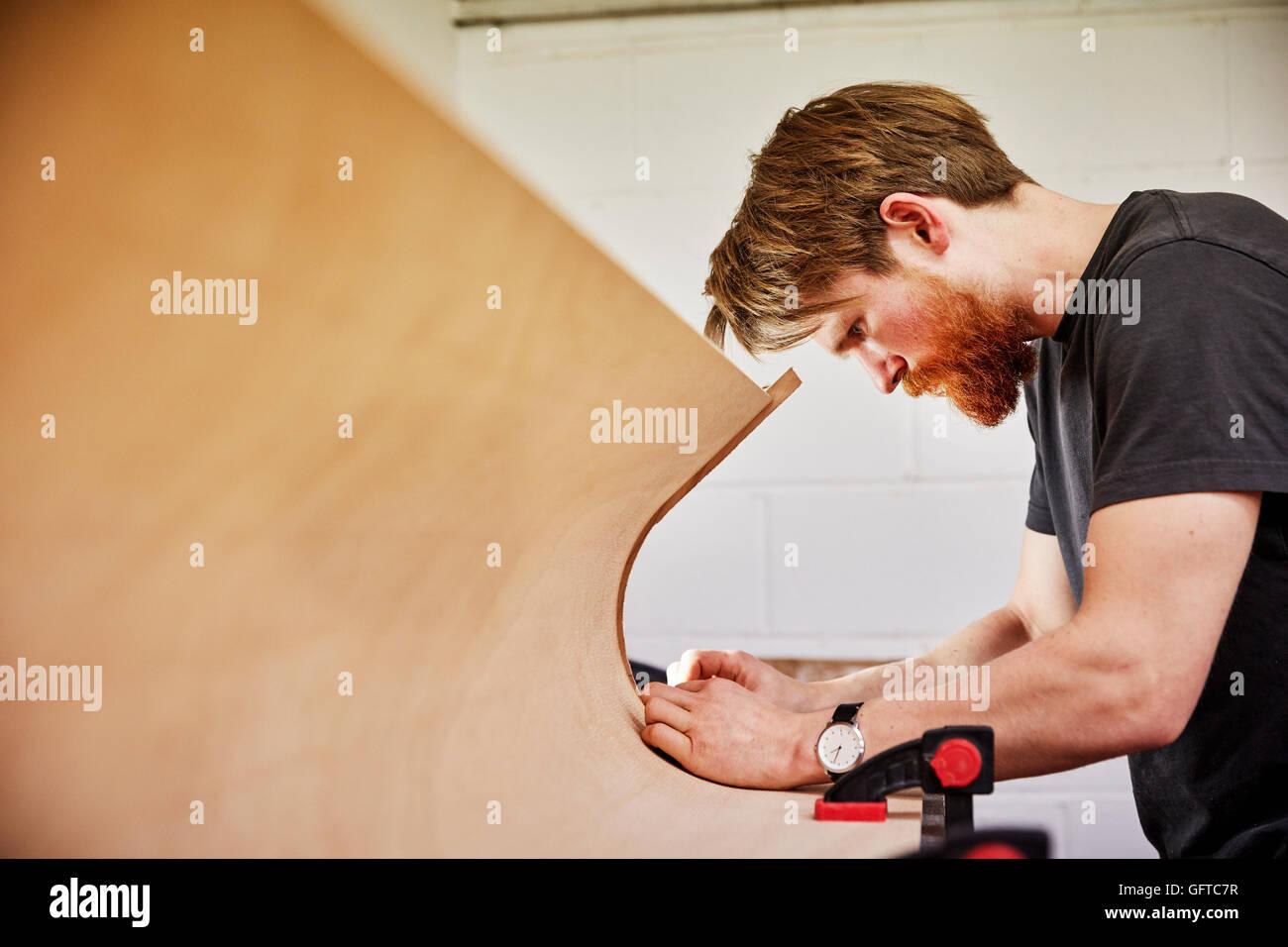 Un homme à l'aide d'un outil sur le bord de coupe courbe hors d'un morceau de bois Photo Stock
