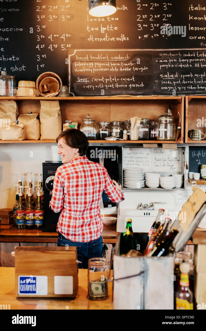 Une femme travaillant derrière le comptoir dans un propriétaire d'entreprise Banque D'Images