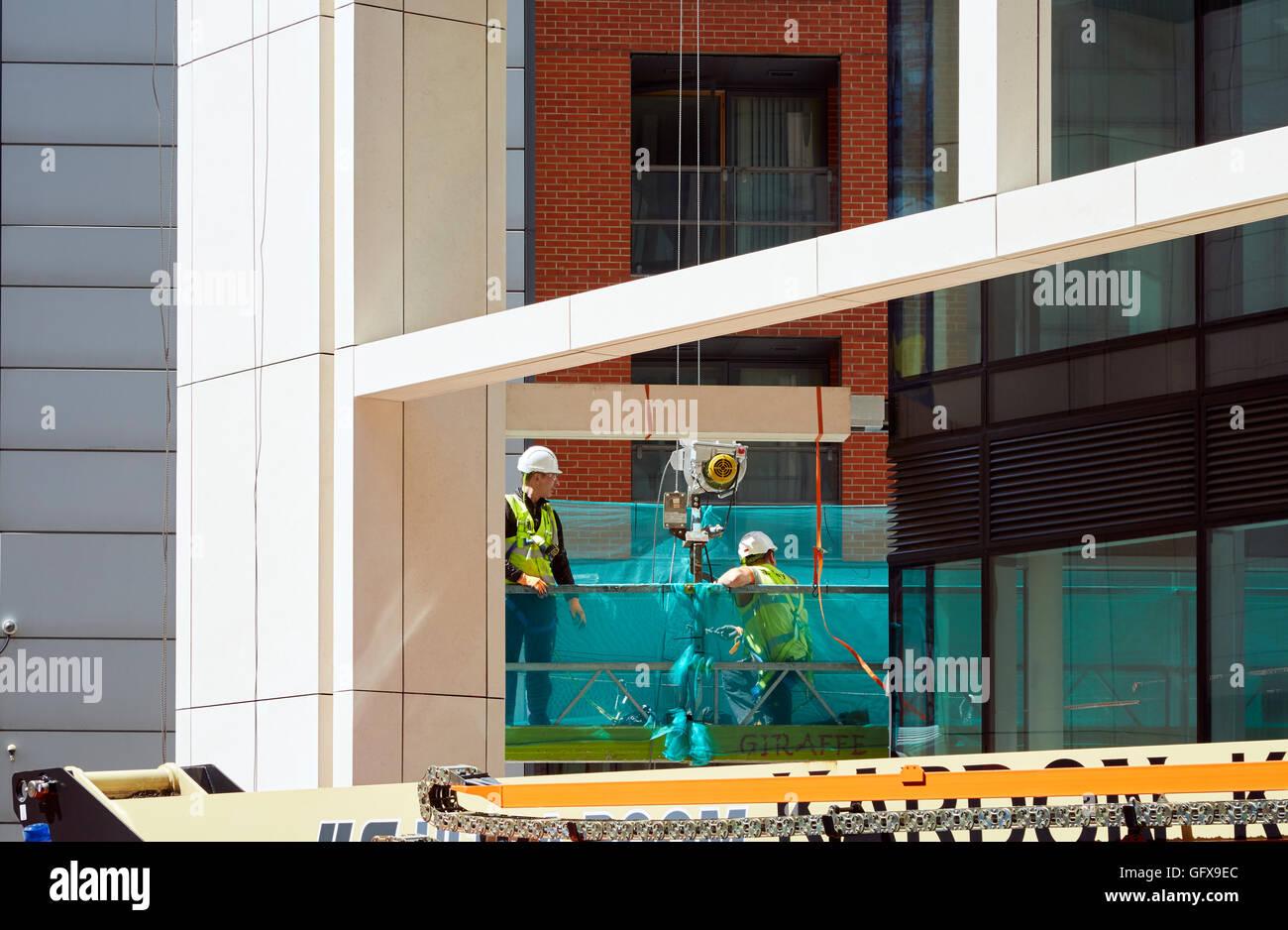 Les constructeurs dans une station de travail sur la construction et l'achèvement de nouveaux bureaux à Photo Stock