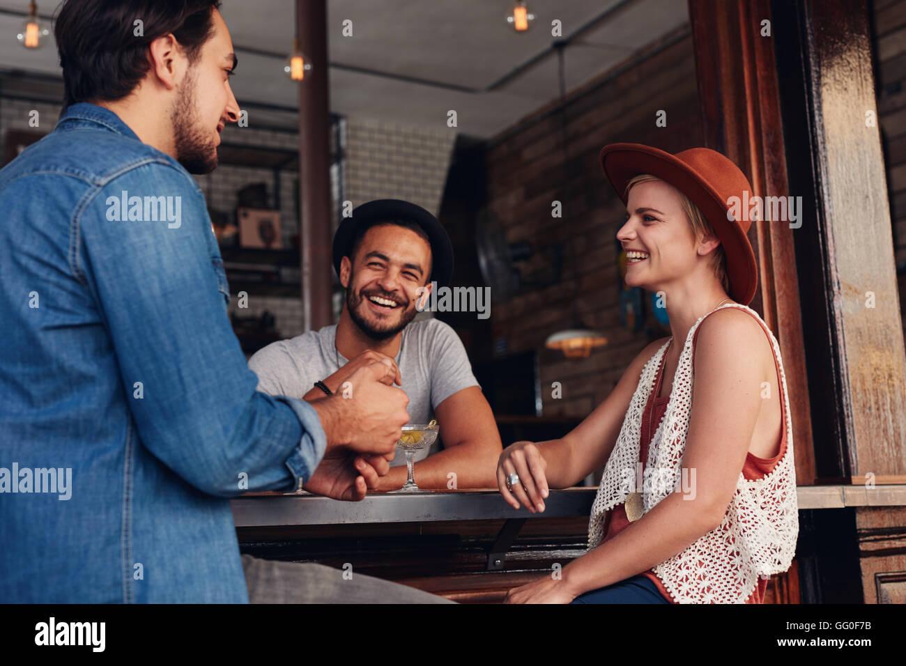 Les jeunes hommes et les femmes siégeant ensemble et parler dans un café. Groupe de jeunes amis dans un Photo Stock
