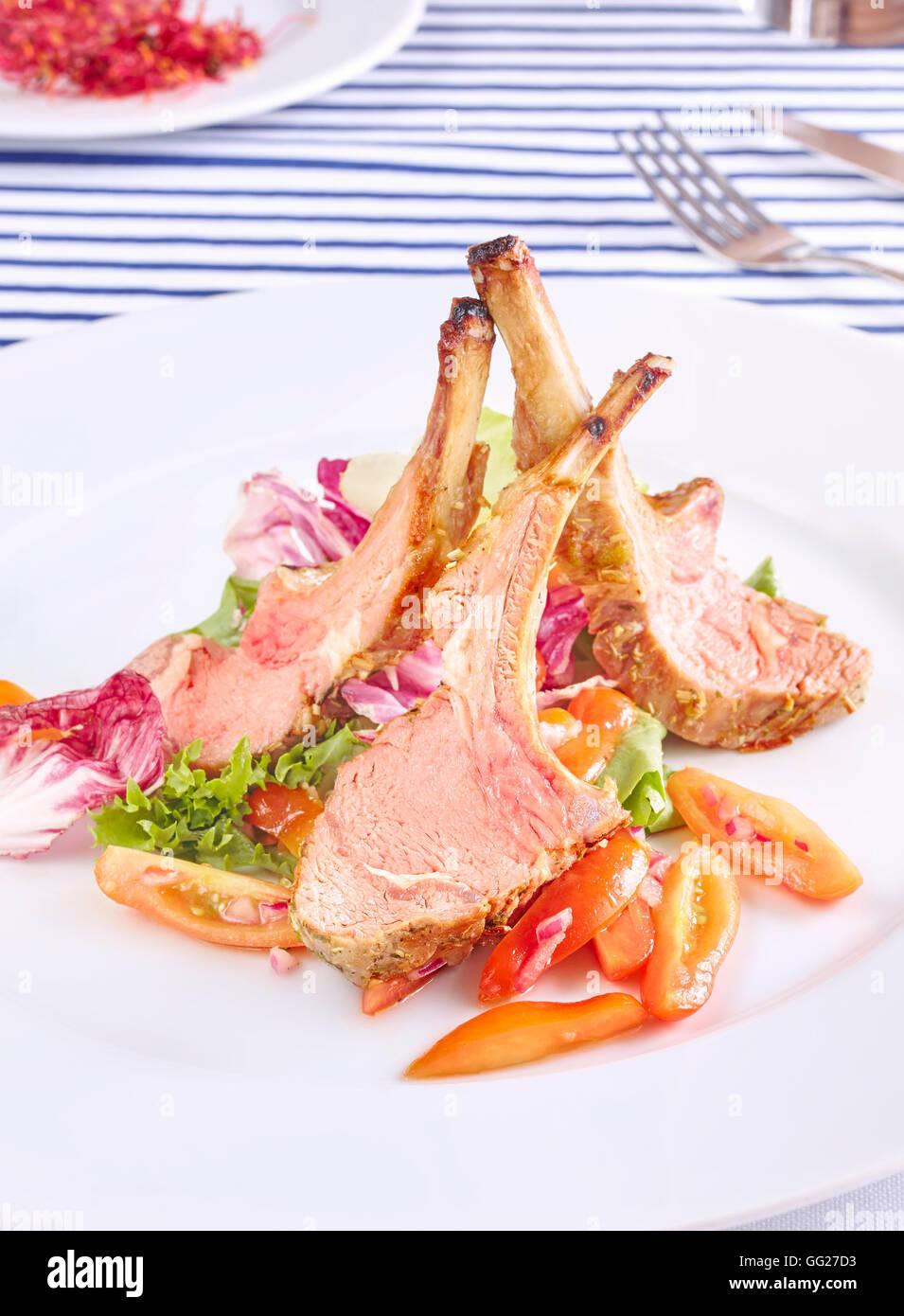 L'agneau rôti côtelettes avec de la salade et des tomates. Photo Stock