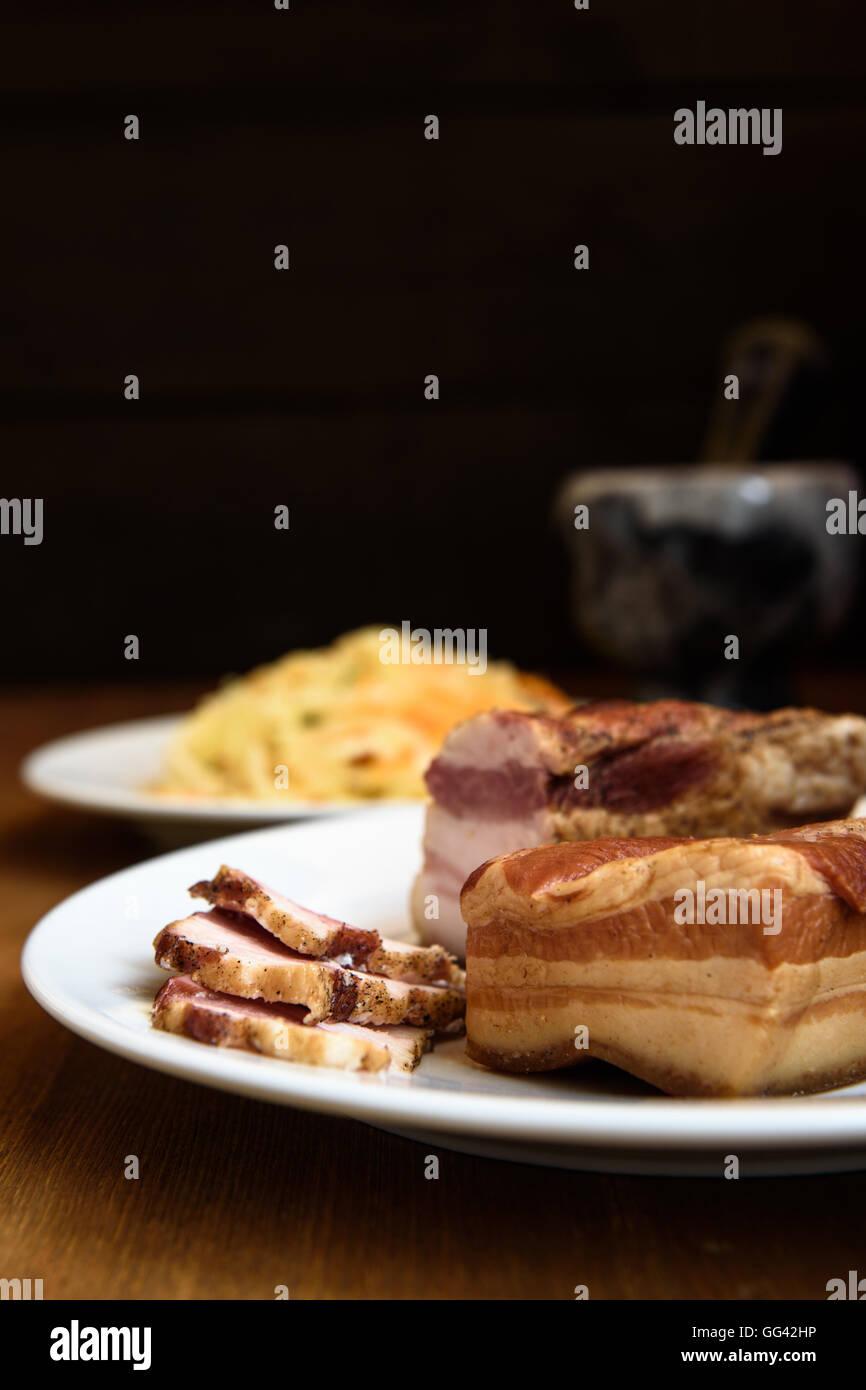 Côtes de porc fumé sur plaque blanche sur fond de bois Photo Stock