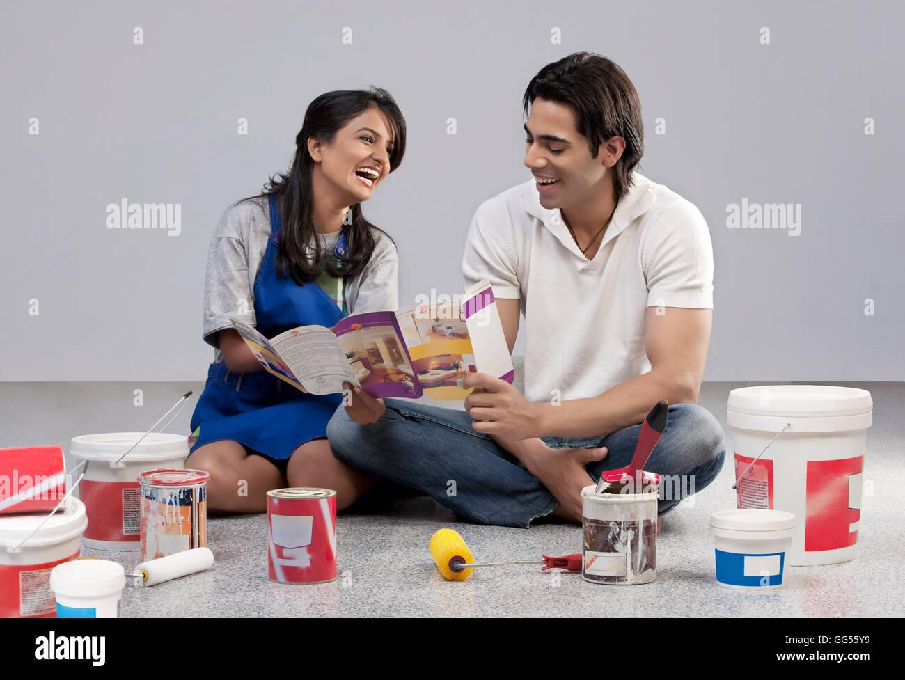 Couple avec une brochure de peinture Photo Stock