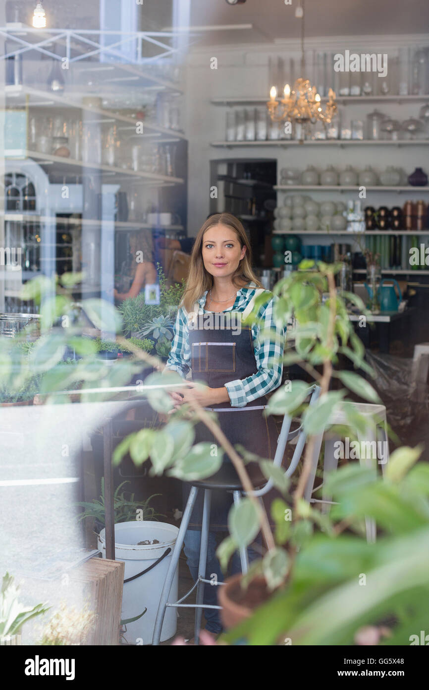 Portrait of a happy woman standing in flower shop Photo Stock
