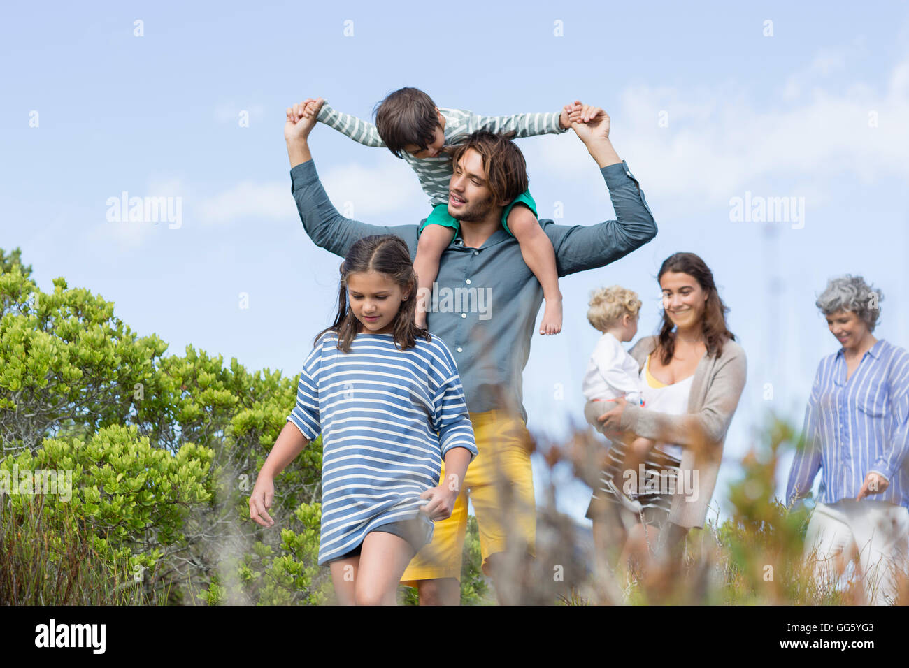 Multi-generation family walking in meadow Photo Stock