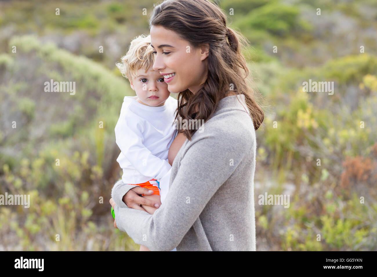 Heureux belle femme portant son bébé Banque D'Images