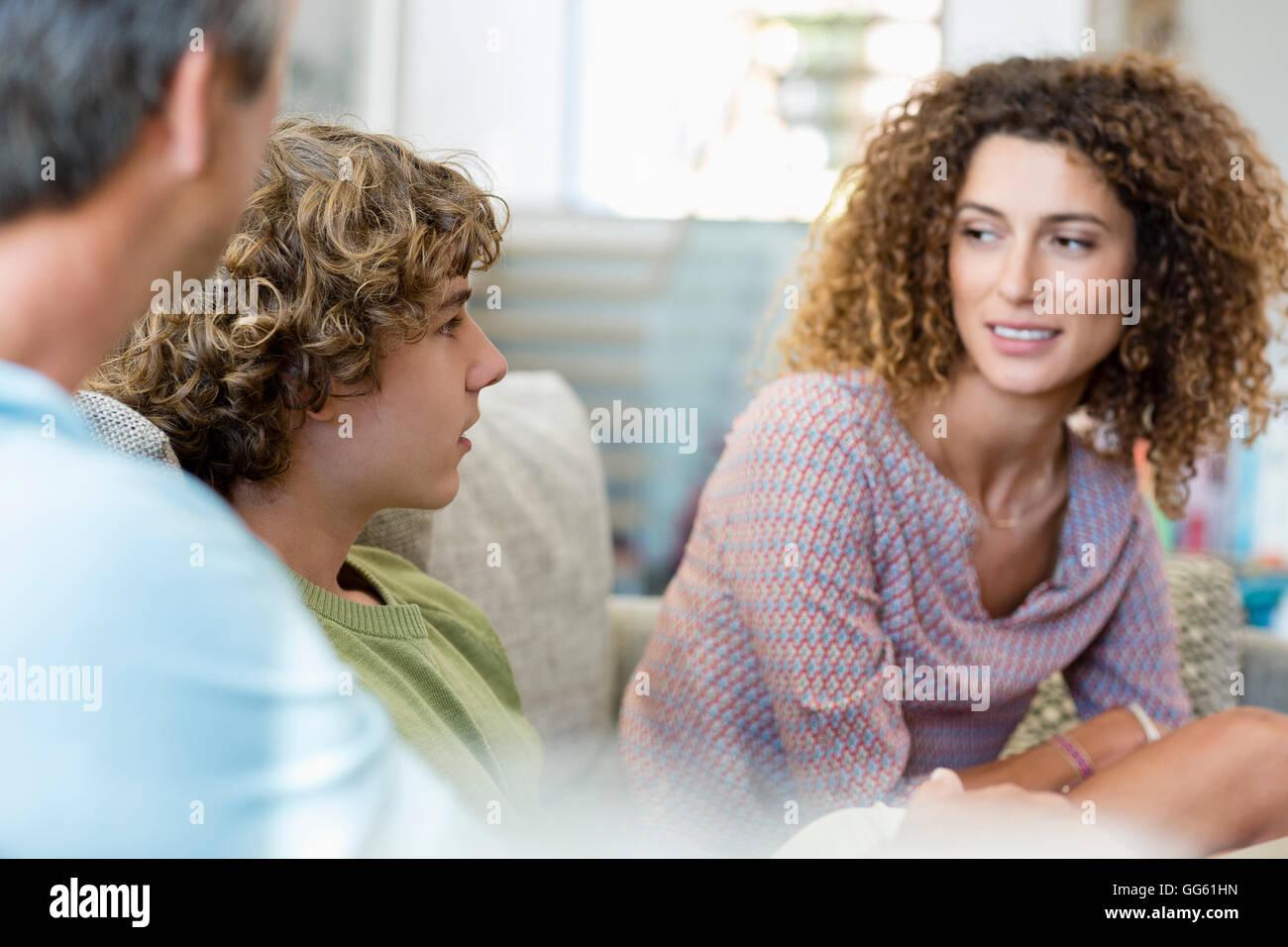 Famille heureuse de parler dans une salle de séjour à la maison Banque D'Images