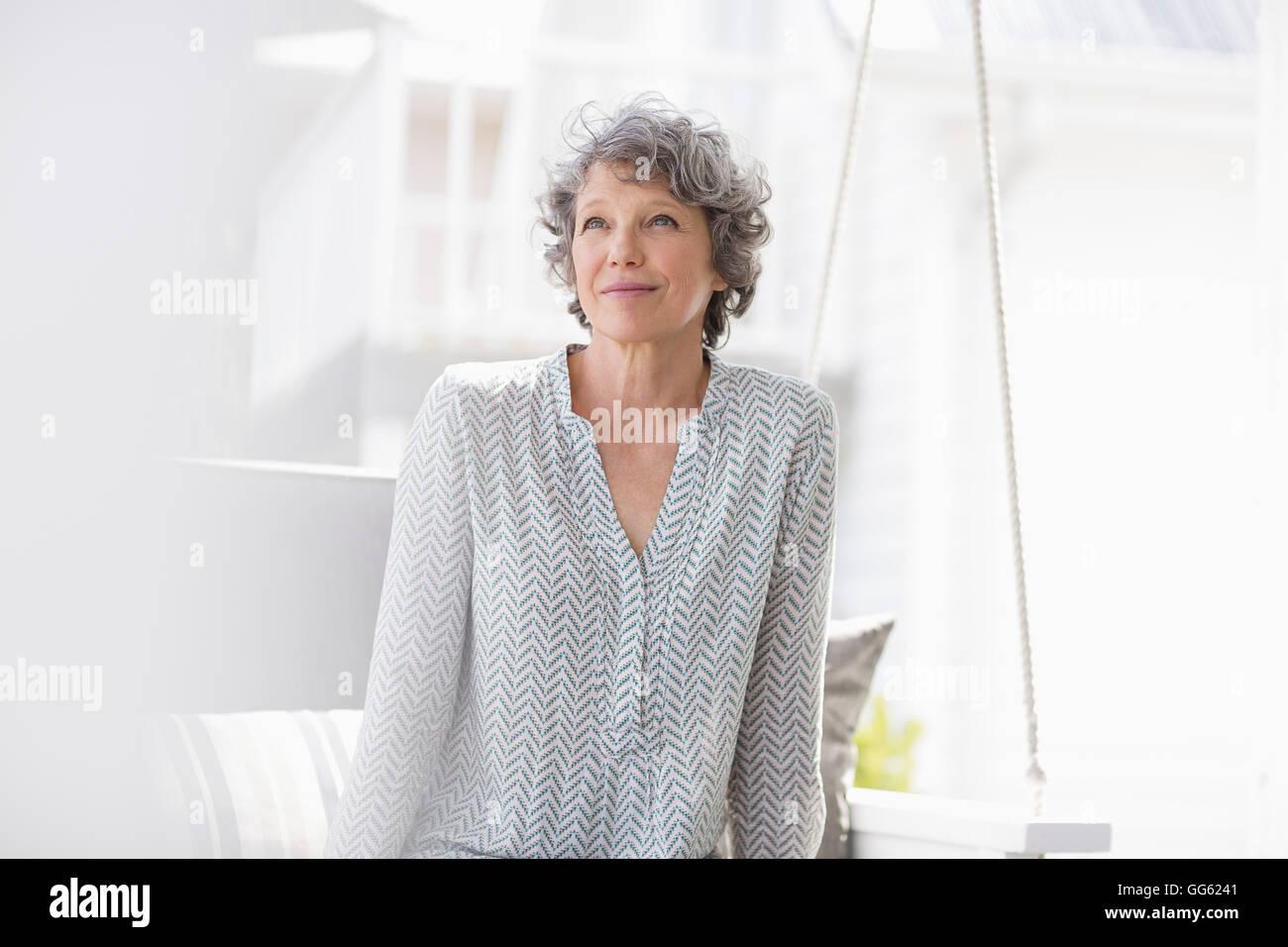 Femme assise sur une balançoire et la pensée Photo Stock