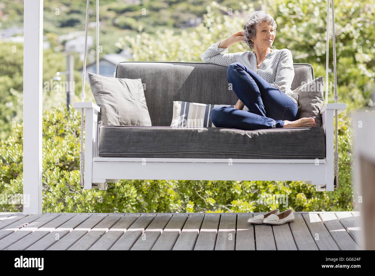 Mature femme assise sur une balançoire dans un porche Photo Stock