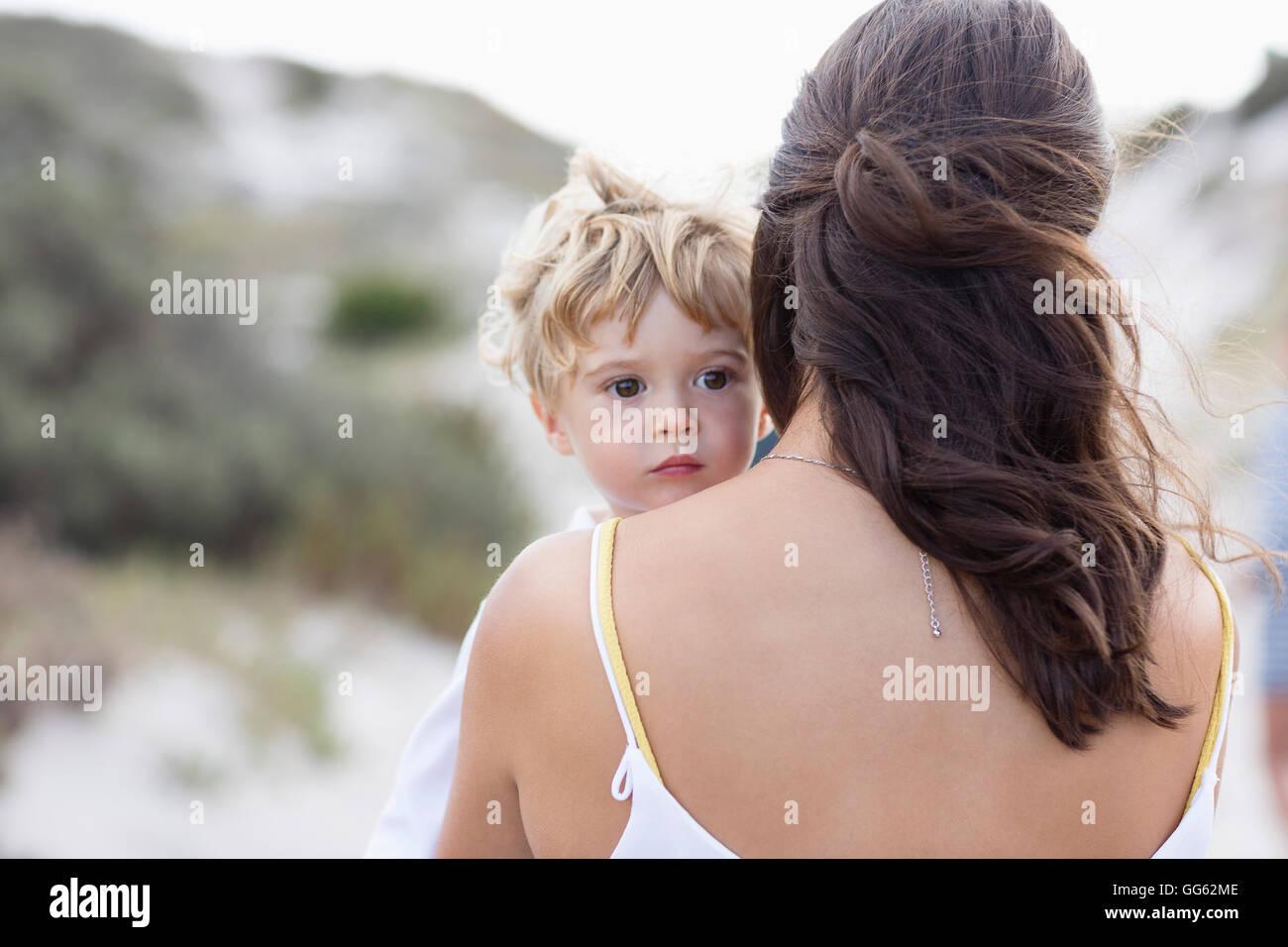 Vue arrière d'une femme portant son bébé Photo Stock