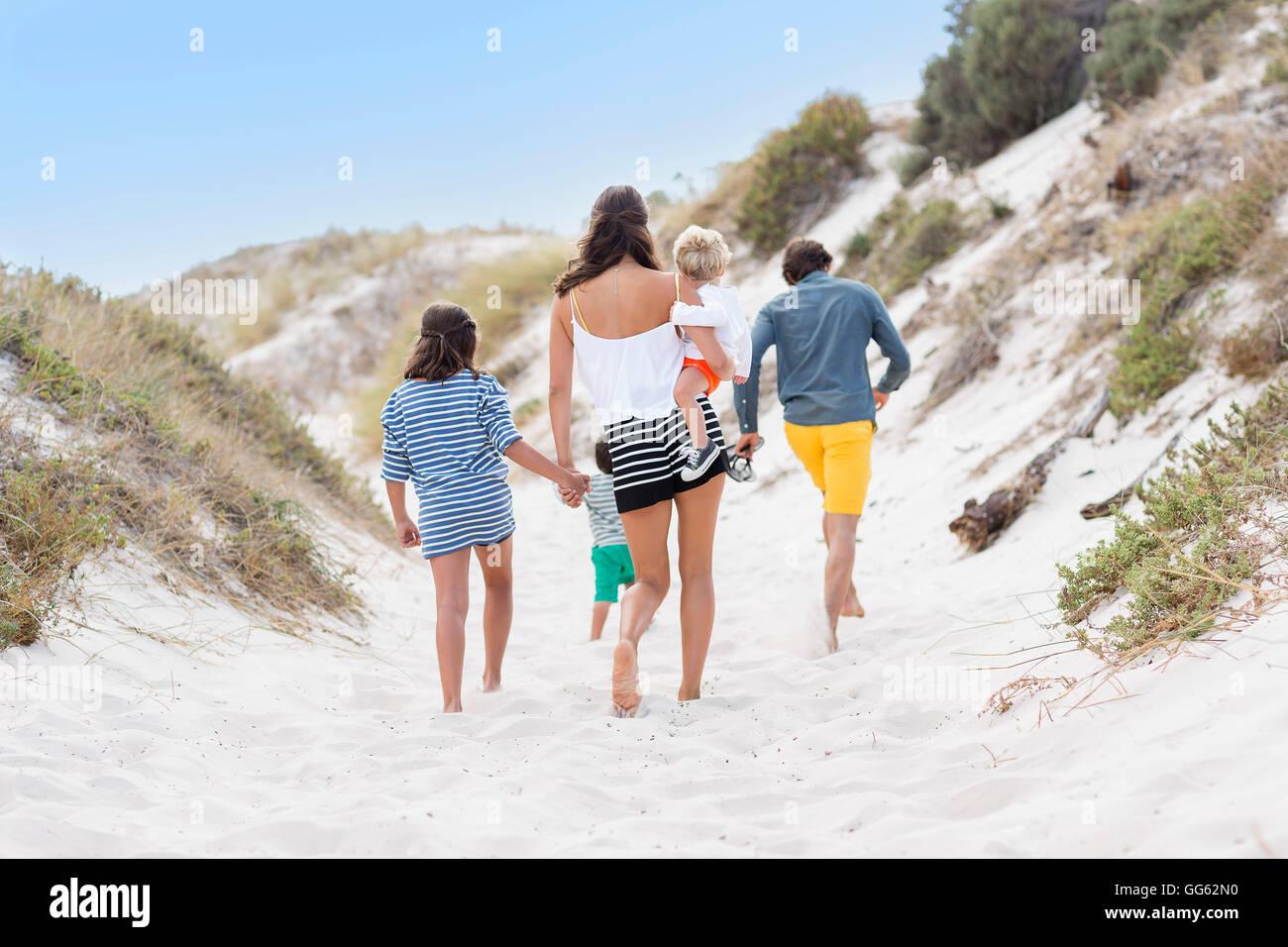 Vue arrière d'une famille marche sur la plage Photo Stock