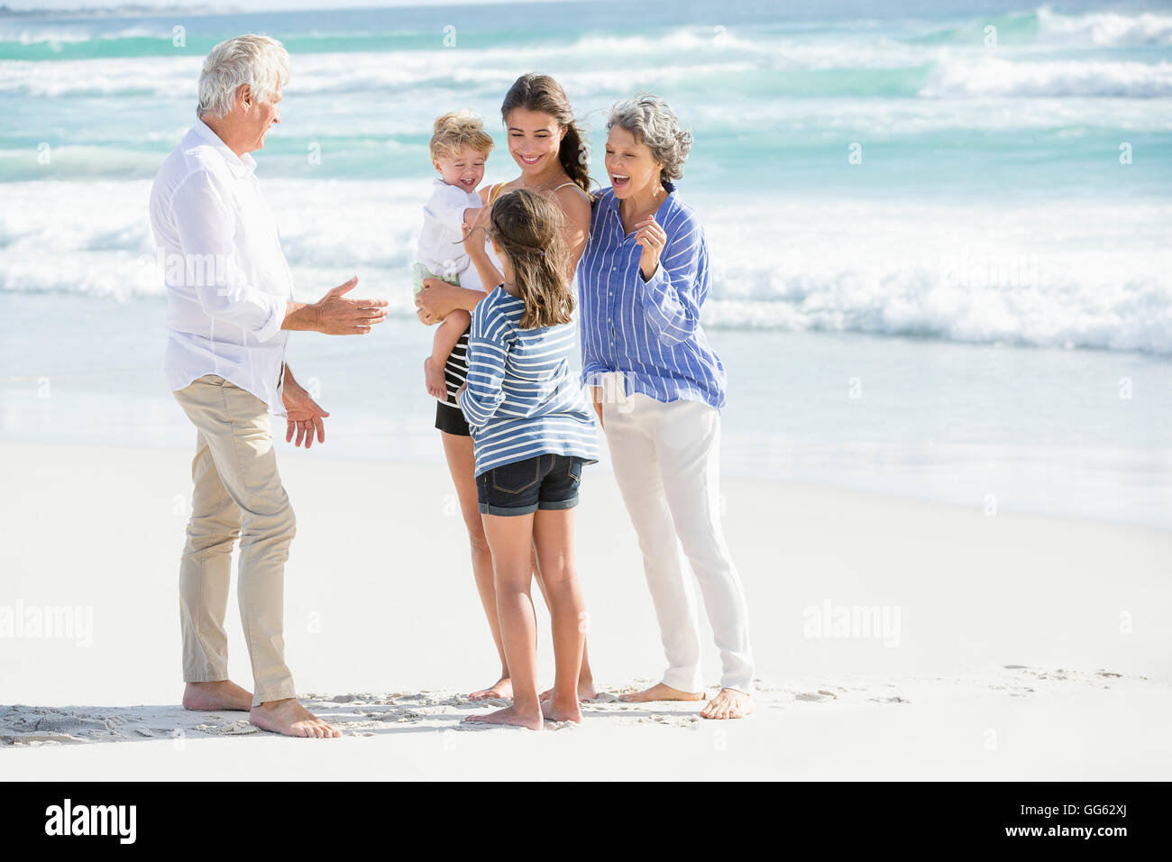 Multi-generation family standing on the beach Photo Stock