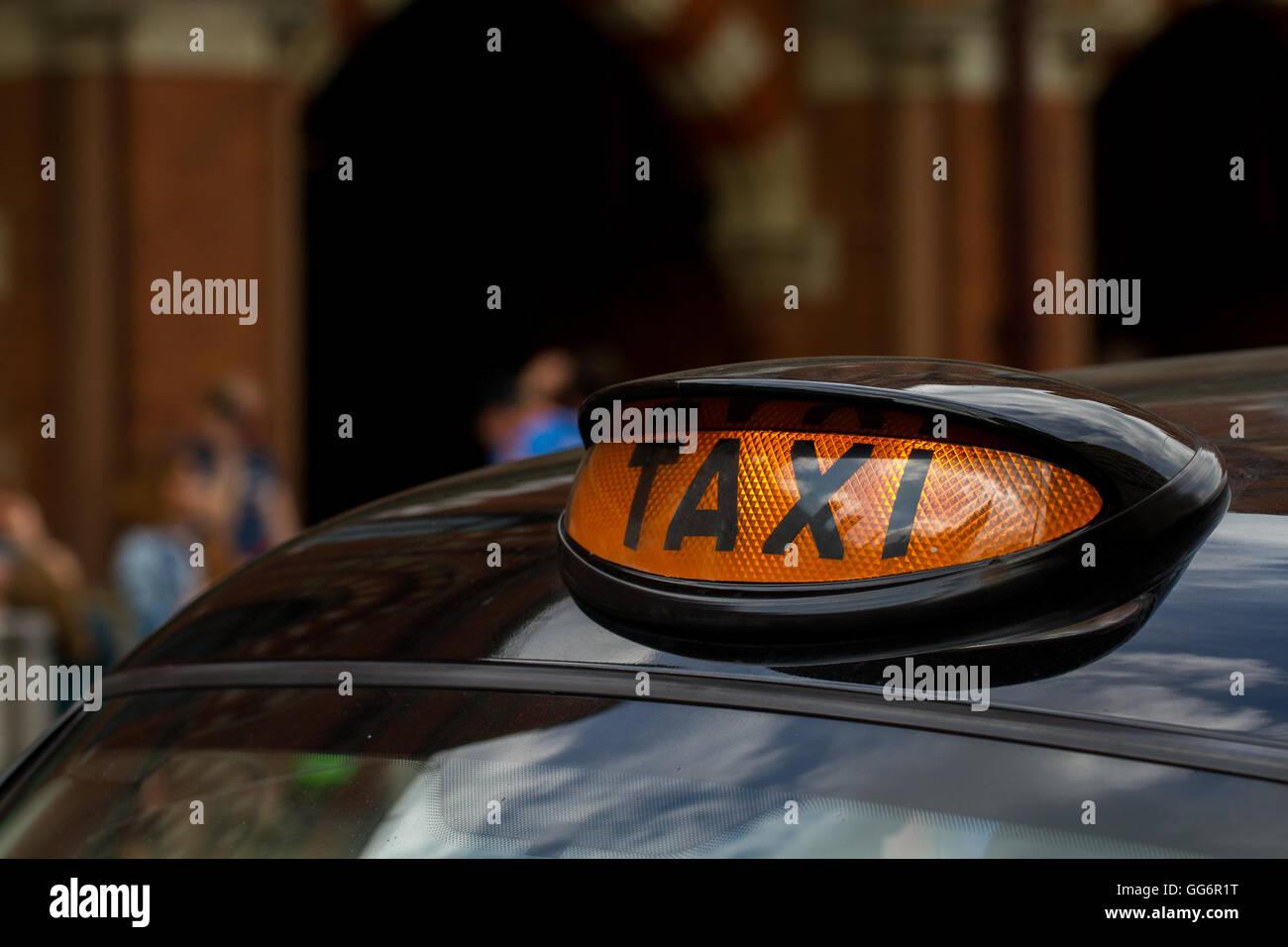L'orange enseigne sur le toit d'un taxi noir de Londres avec les rues de la ville en arrière-plan. Photo Stock