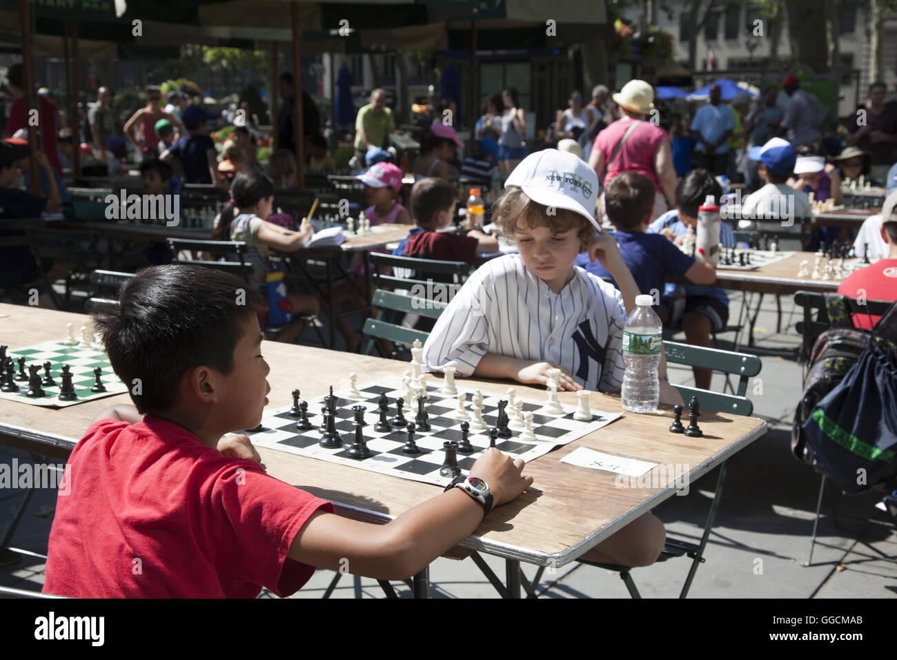 Les enfants à apprendre et jouer aux échecs à l'occasion d'une journée d'échecs (camp) dans Bryant Park à Manhattan, New York. Banque D'Images