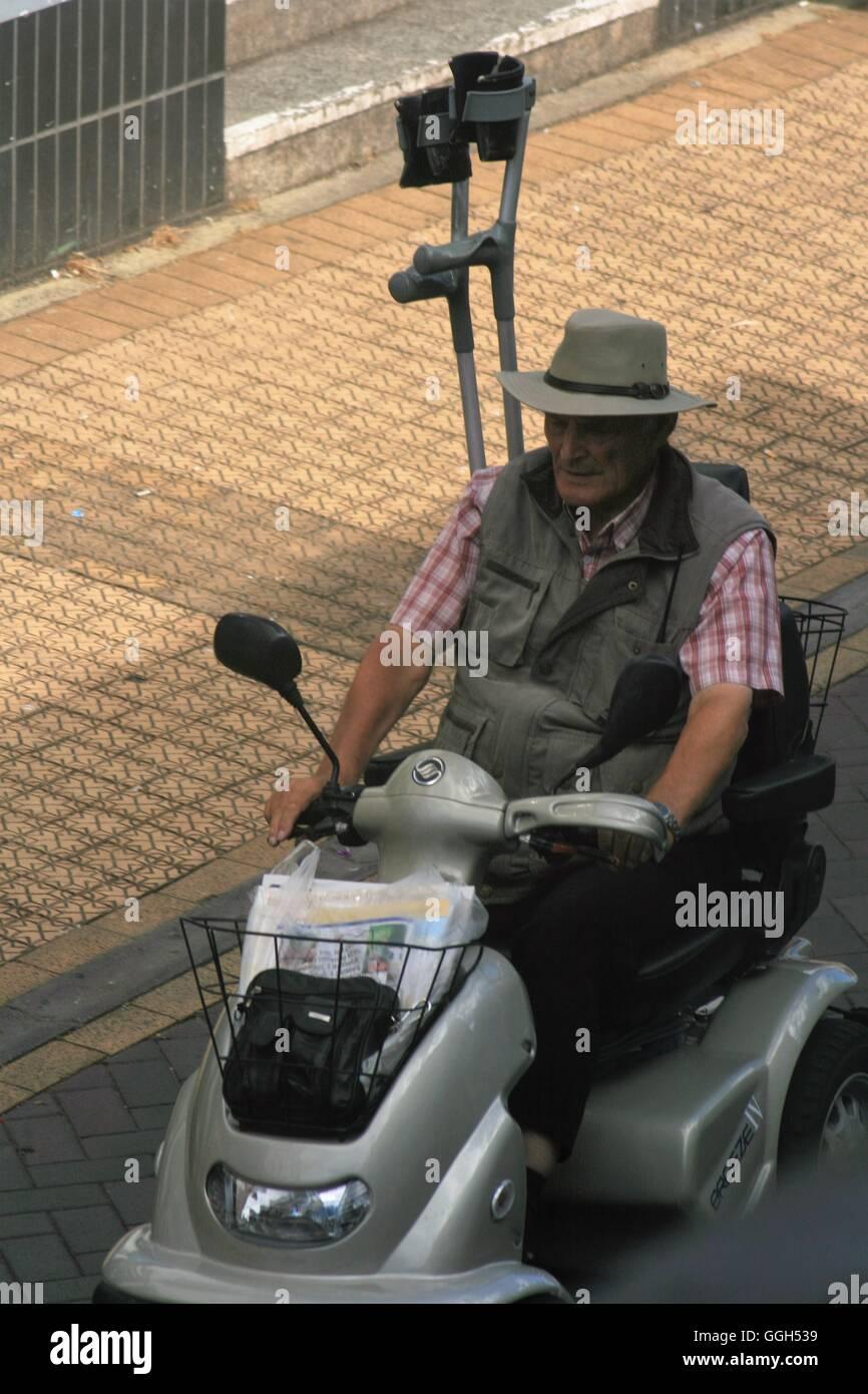 Un homme âgé de la conduite dans la ville sur un scooter de mobilité avec des béquilles rangé Photo Stock