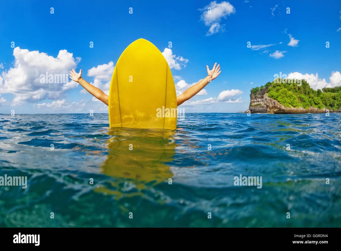 Les jeunes professionnels surfer girl avec diffusion de mains s'asseoir sur le surf board et a l'amusement. Photo Stock