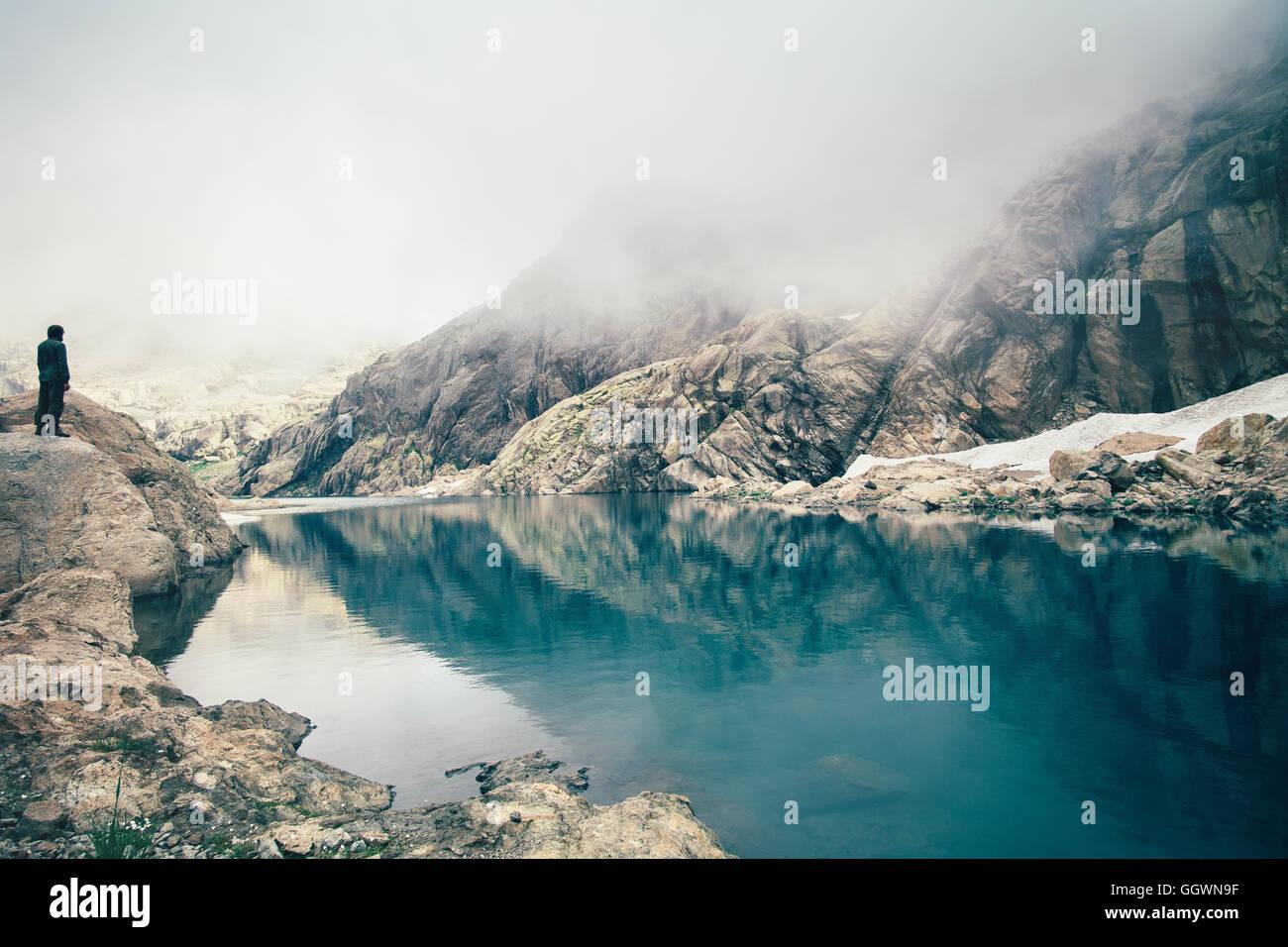 Man Traveler Standing alone on Cliff Lake et de montagnes brumeuses sur le contexte de vie de plein air concept Banque D'Images