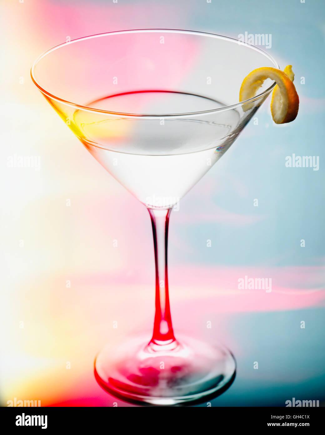 Vue rapprochée d'un verre de martini avec une torsion dans une lumière colorée Photo Stock