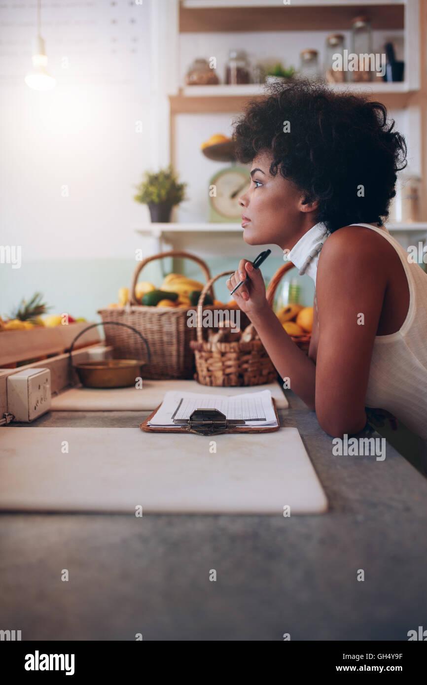 Side portrait of young woman standing au comptoir de bar de jus à l'écart et la pensée. Femme africaine sérieuse bar à jus propriétaire. Banque D'Images