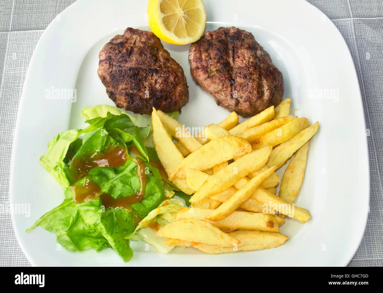 Hamburger grillé avec des frites de pommes de terre - la nourriture grecque Banque D'Images