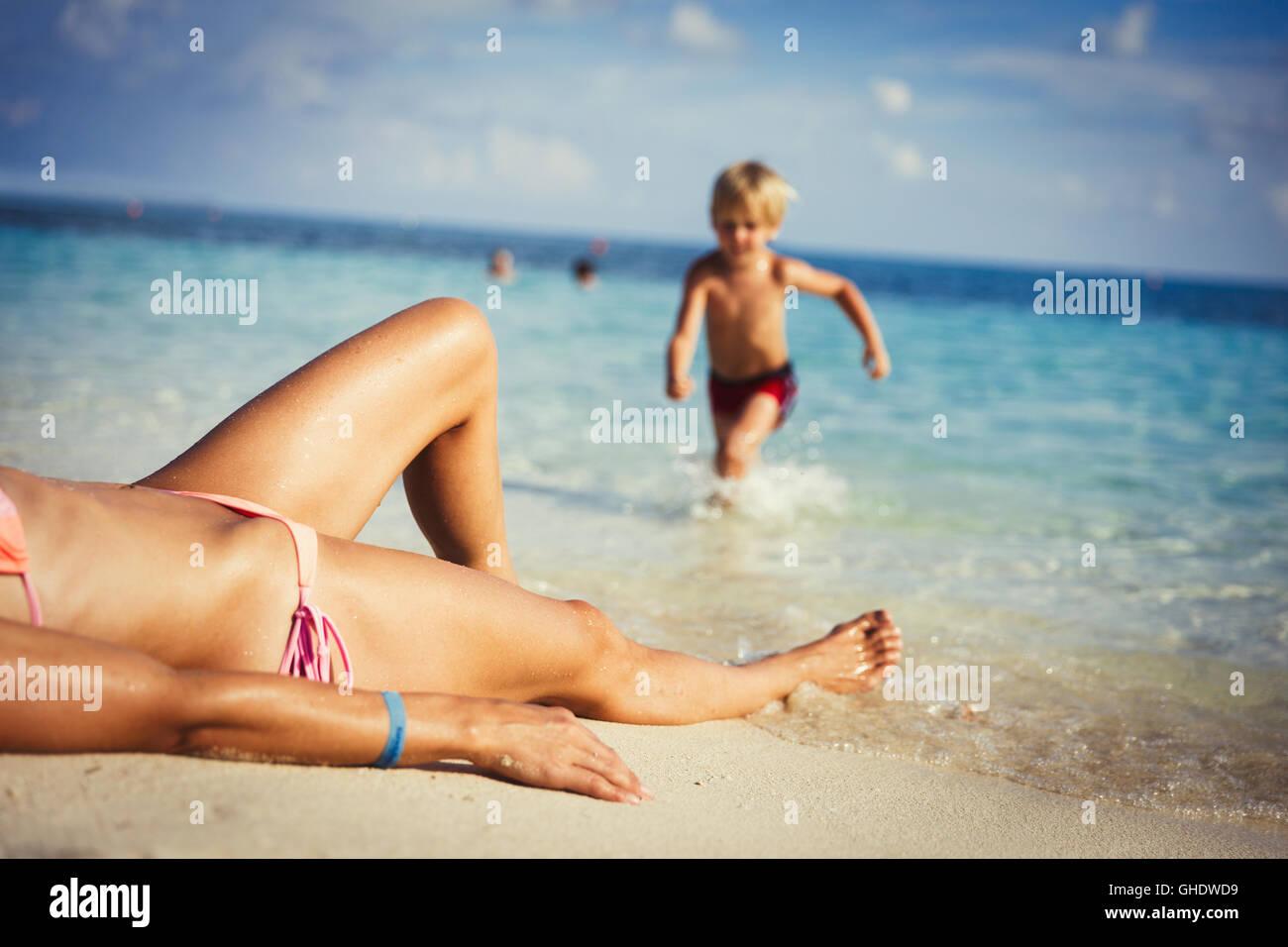 Fils d'exécution vers mère de soleil sur plage tropicale ensoleillée Banque D'Images
