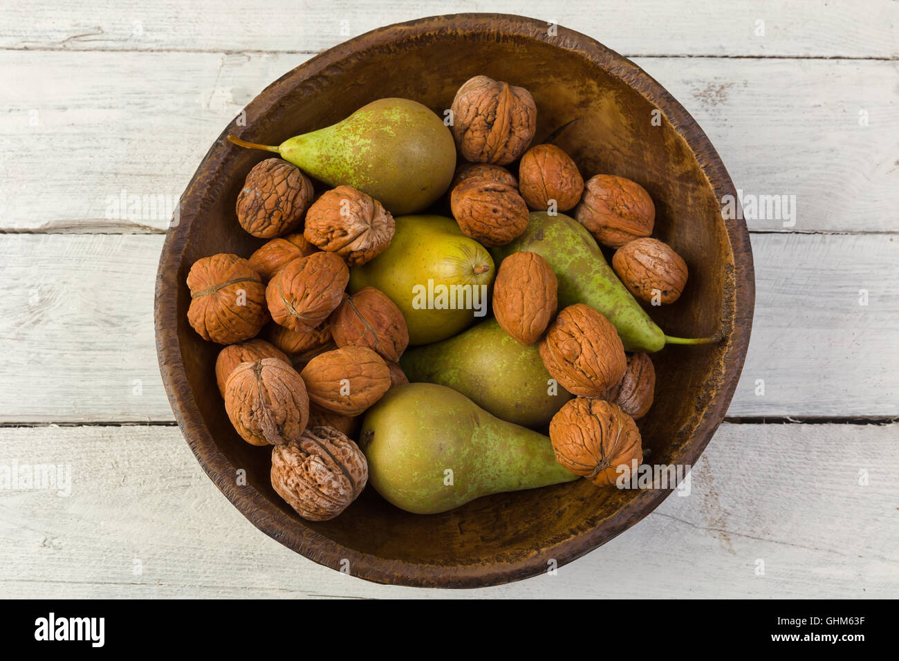 Automne Nature morte avec un bol de poires et les noix sur une grunge background Photo Stock
