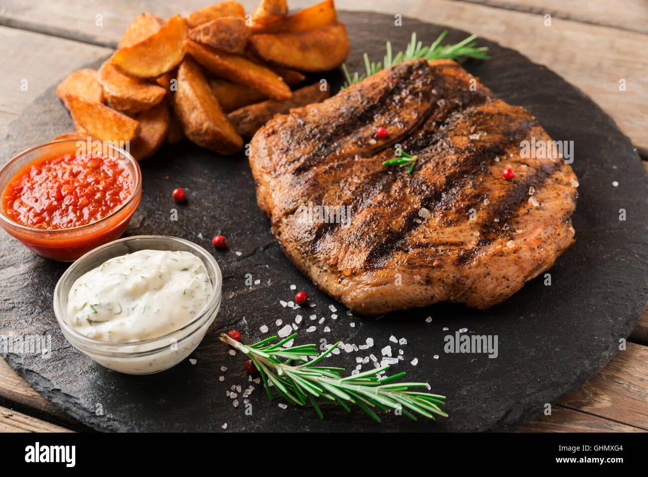 Pavé de boeuf avec pomme de terre au four et sauce Photo Stock