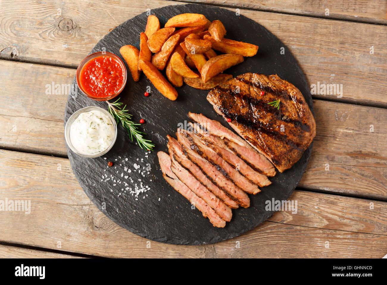 Pavé de boeuf en tranches avec pomme de terre au four et sauce Photo Stock
