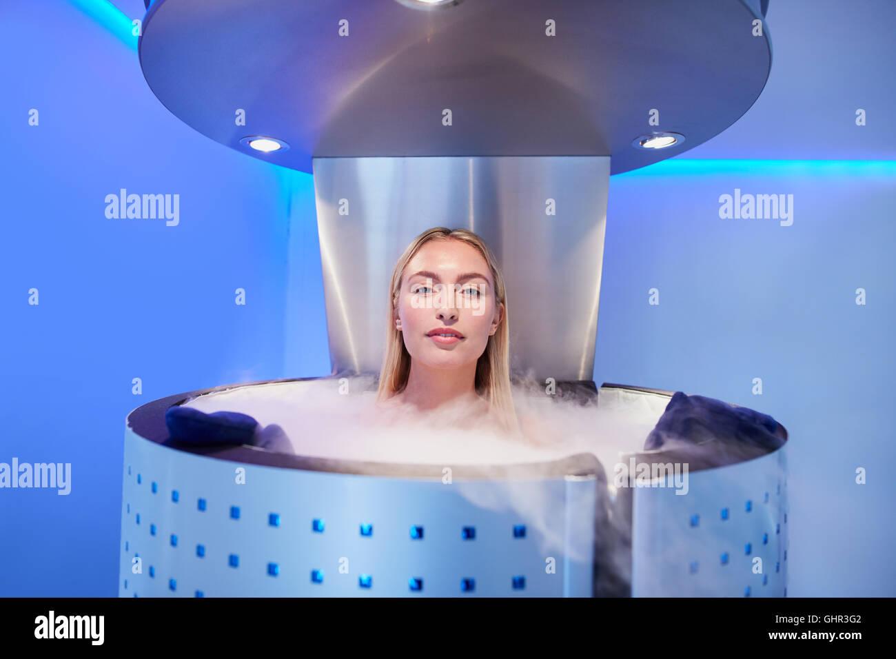 Femme en cryosauna stand pour la cryothérapie du corps entier. Les femmes de race blanche dans la pièce Photo Stock