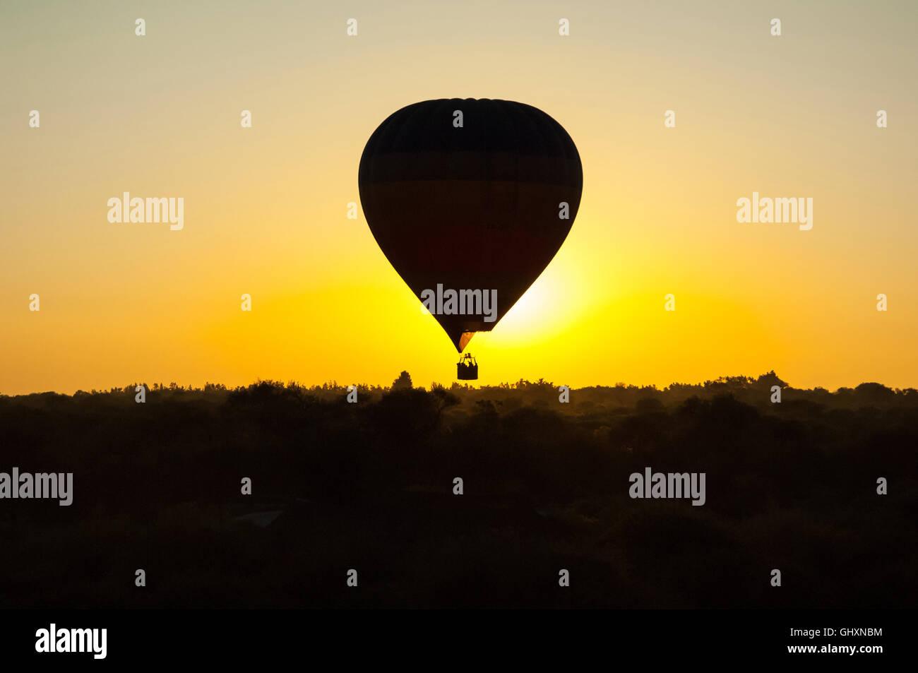Silhouette de montgolfière en ciel sans nuages au lever du soleil sur la plaine africaine misty Photo Stock